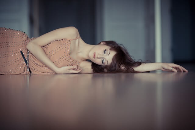 沈んだ表情で横たわる女性